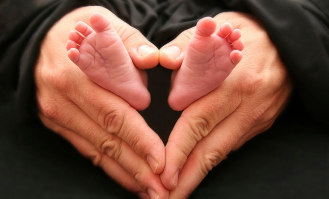 This is a photo of a dad with his hands in a heart shape holding his 3 week old infants feet.
